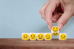 Person picking up cubes with emoji faces on them