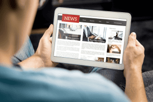 a person holding a tablet and reading the news